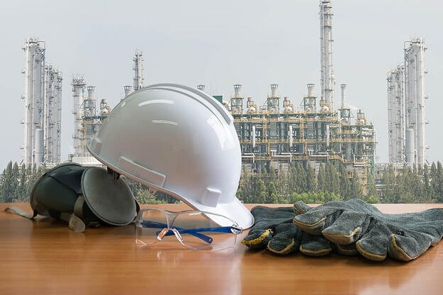 Safety work wear in front of refinery background