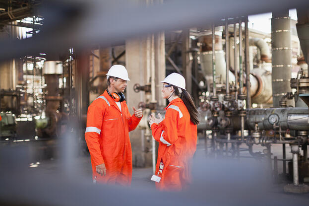 iStock-149319768-Workers_talking_at_oil_refinery_stock_photo