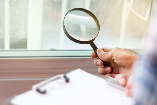 inspector holding magnifying glass over checklist